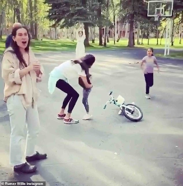 Modern family: Bruce Willis and Emma Hemming's daughter Evelyn learn to ride a bike in their latest Instagram post, including ex-wife Demi Moore and their daughters