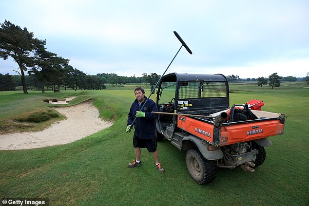 A bunker is raked next to the first green of the new course by a member of the green staff team at the Walton Heath Golf Club in Tadworth, Surrey
