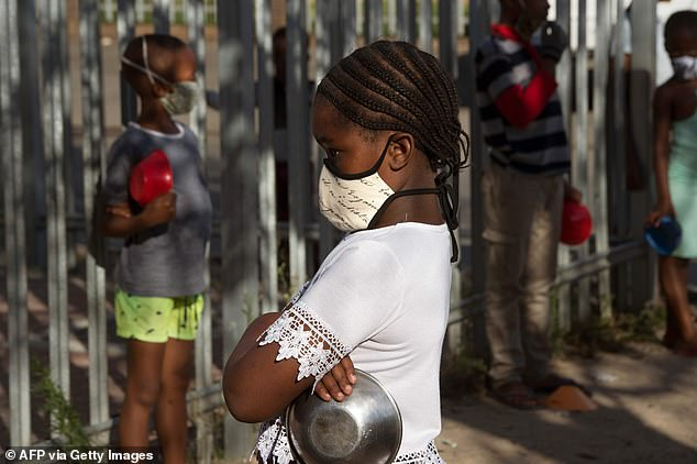 Pictured, children wait in lines in near Cape Town on May 14, 2020, to receive a meal.South Africa has the most infections of all African nations, with almost 13,000 confirmed cases