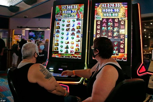 Nationwide, some 500 Native American casinos have shut down. Pictured: Gladys Whittington (left) and Sandy Christian (right) play at a gaming machine at Lucky Star Casino, May 15