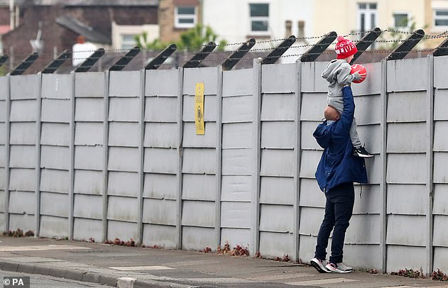 Man lifts child so he can look over fence at Melwood base in Liverpool Tuesday