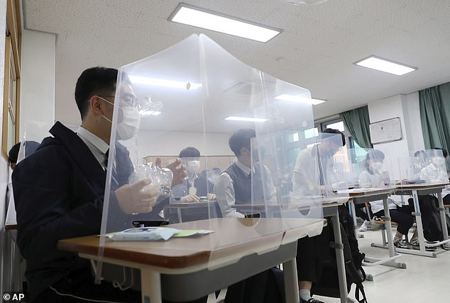 Senior students wait for a class to begin with plastic shields placed on their desks at Jeonmin High School in Daejeon, South Korea, Wednesday, May 20, 2020