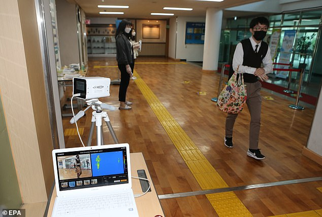 A student walks past a thermal scanner to have his temperature checked before entering class at Geumcheon High School in Cheongju, South Korea, 20 May 2020