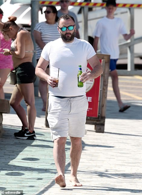 A man in Bournemouth walks bare-foot as he carries a beer and a small drink