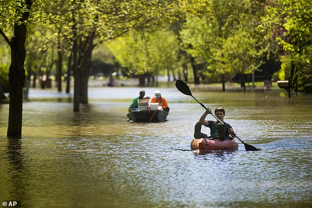 Hunter Klich, 14, maneuvers a kayak down the middle of Walden Woods Drive in Midland as residents coped with flooding