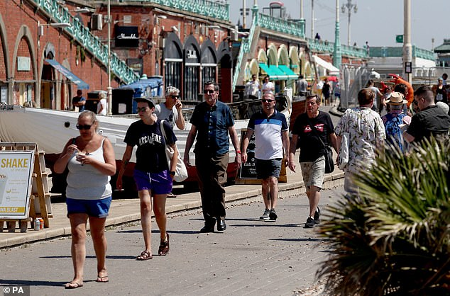 A snapshot by the Office for National Statistics found that 137,000 – 0.24 per cent of the population – had the virus. Pictured: The promenade in Brighton was thronged with visitors on Thursday