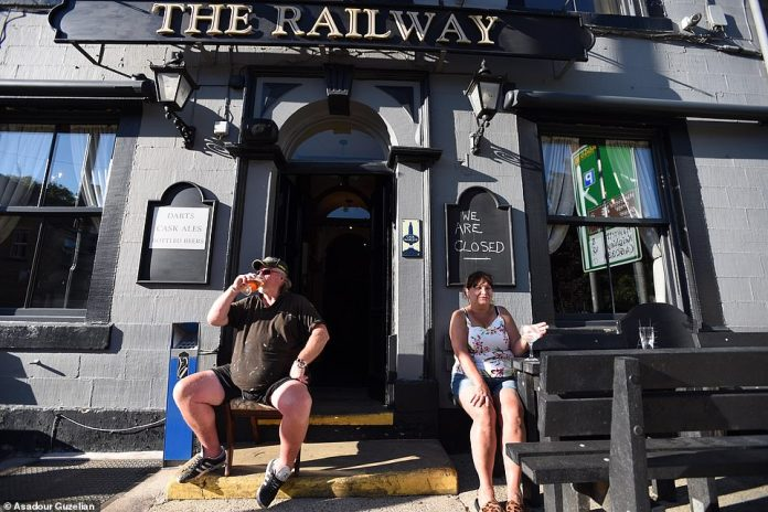 Kaomi and Mick Jones, owner and owner of the Hebden Bridge Railway, have a drink outside their closed pub on the hottest day of the year this week. They caught the attention of the police until they explained to the officers that they were within the confines of their home.