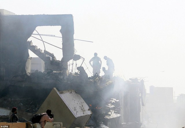 Emergency crews inspect the destruction as they stand in the rubble after the plane smashed into buildings on Friday