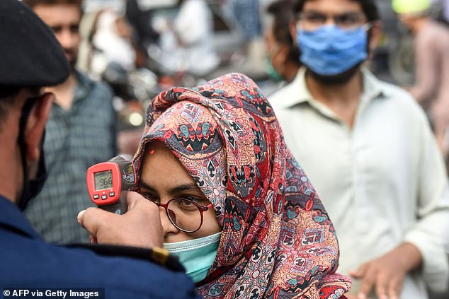 Ashopping mall official checks the body temperature of a customer arriving for shopping ahead of the Eid al-Fitr festival which marks the end of the Muslim holy month of Ramadan in Karachi, Pakistan