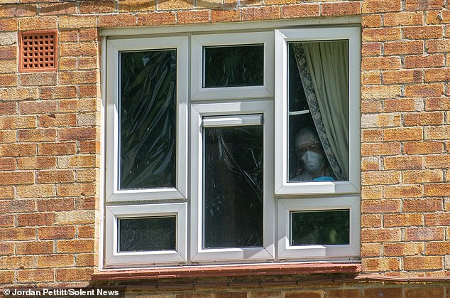 A forensic officer blacks out windows at the property in Leigh Park after a body was found in woodlands