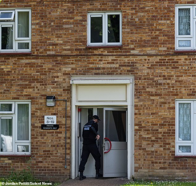A police officer enters the property in Leigh Park after a body was found in woodlands yesterday