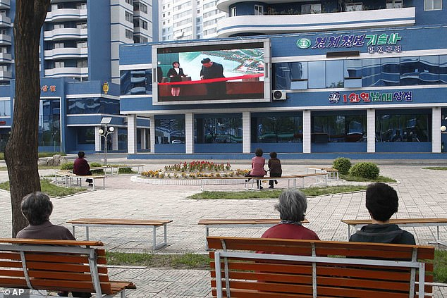 North Korean media have for years propagandized myths about the Kim family, perpetuating beliefs that they are capable of superhuman feats. Pictured: Residents ofPyongyang, the capital of North Korea, watch Kim Jong Un's first supposed public appearance on large screens, May 1