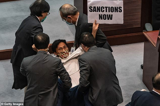 Eddie Chu, a pro-democracy lawmaker, is removed by security during a scuffle with pro Beijing lawmakers