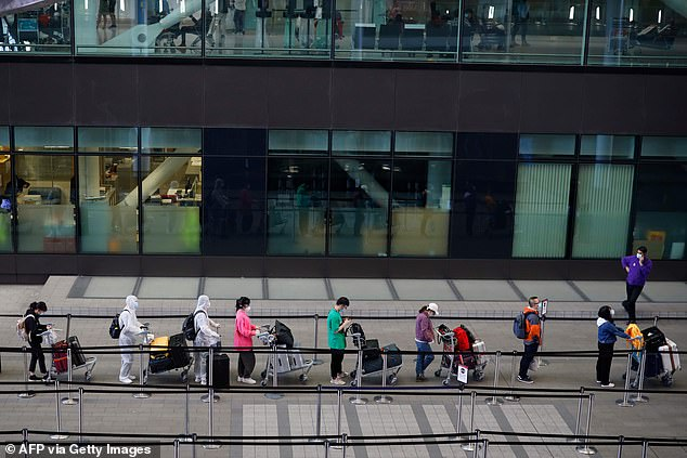 Passengers wearing personal protective equipment line up to board a flight at Heathrow Airport today