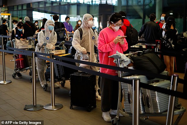 Antivirus passports and travel lanes could allow families to travel abroad this summer. Pictured: Passengers wearing PPE line up to board a flight to China at Terminal 2 at Heathrow Airport today