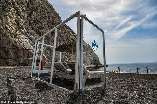 Plexiglas panels protect a parasol and deckchairs as a preventive measure to slow the spread of the coronavirus in Santorini