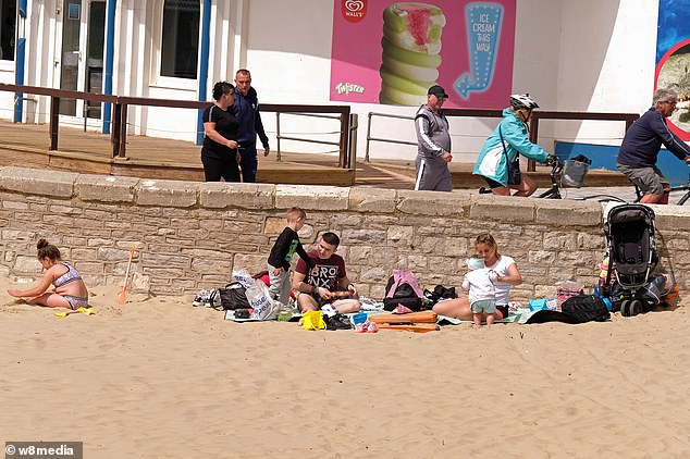 People are pictured on the beach in Bournemouth today ahead of improving temperatures set to hit Britain on the Bank Holiday