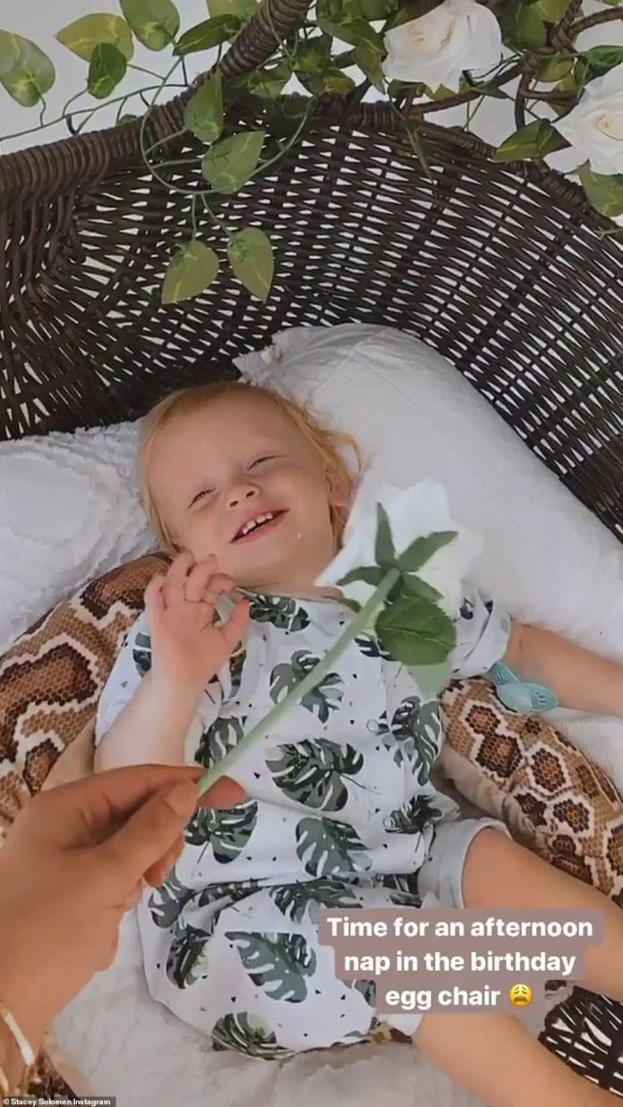 Giggles: Stacey shared a video of him lying down while she tickled his face with one of the flowers she had earlier attached to the chair