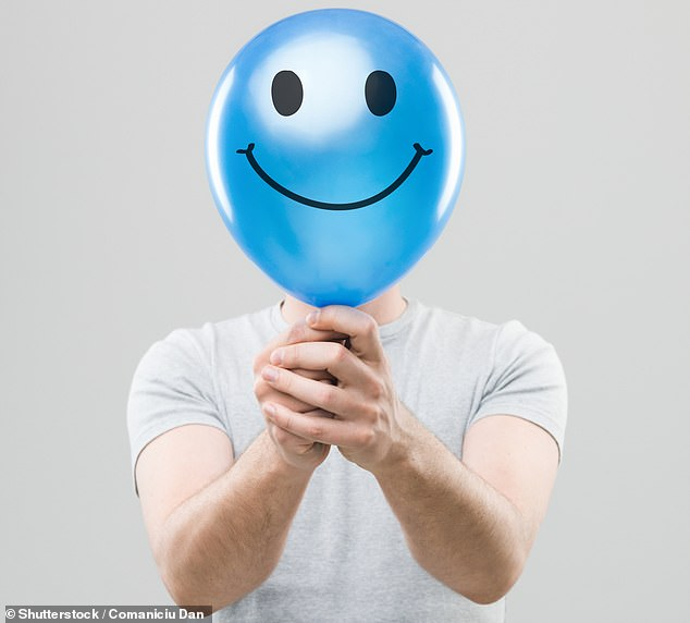 Am I suffering from depression... and how do I stop panic attacks? (pictured: a man hiding his face behind a blue balloon with a smiley face drawn on it)