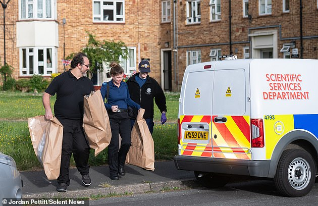 Pictured: police carry bags at a house in Leigh Park, Hampshire