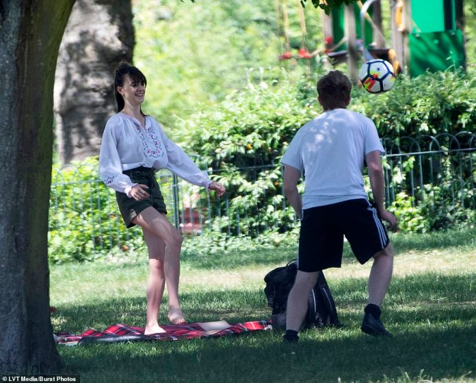 Fun and laughter: Daisy smiled broadly as he kicked her boyfriend soccer