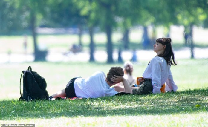 And relax: Daisy sat back down while Tom lay down as they relaxed on their picnic blanket