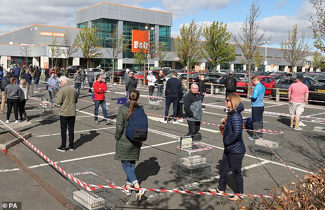 Members of the public follow social distancing guidelines and queue in the car park of B&Q in Edinburgh as they wait to enter the store