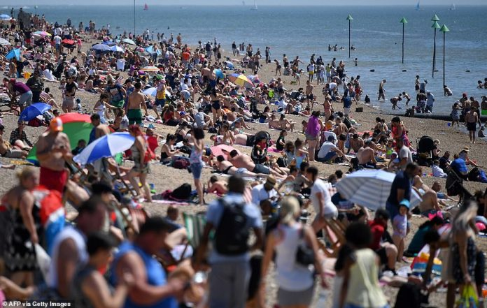 Beach goers soak up the sun by sunbathing on the beach and playing in the sea on a crowded beach today in Southend, Essex