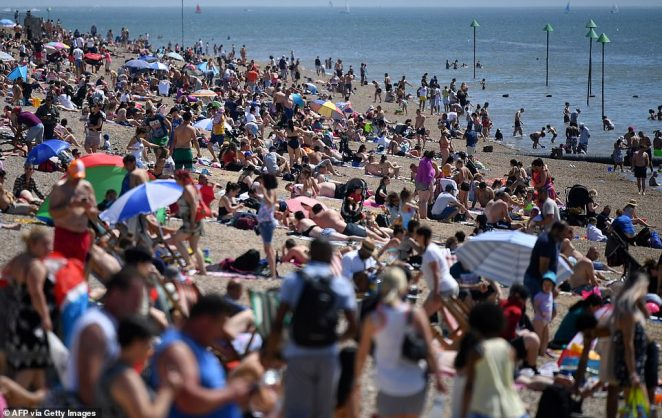 Beach-goers enjoy the sunshine as they sunbathe on the beach and play in the sea at a packed beach today in Southend, Essex