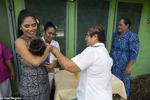 The dark-haired beauty went from home to home to deliver the vital jabs, while emergency medical teams from all over the world – including the UK – helped staff in the overwhelmed hospitals (pictured holding a baby while they are vaccinated)