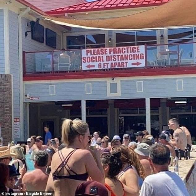 Despite a sign at Shady Gators asking people to keep six feet apart, people are seen crowding around the packed venue