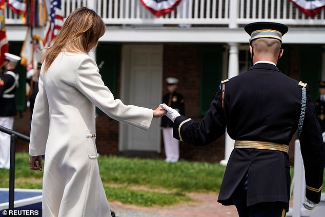 Melania Trump is escorted by a military aide during a Memorial Day ceremony at Fort McHenry