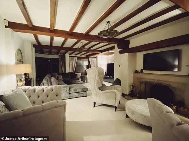 Comfortable: It also has a large flat screen TV while the living room leads to the family room which has another TV with a smaller cream sofa and an armchair.