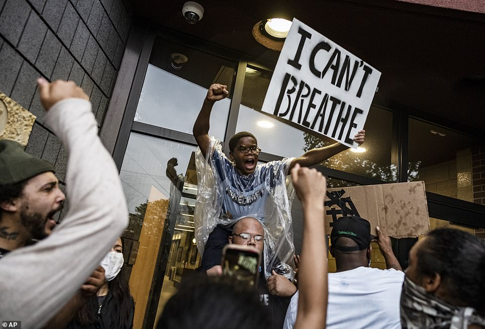 Others held up banners saying 'I can't breathe' as they demanded an end to police brutality against African-American men
