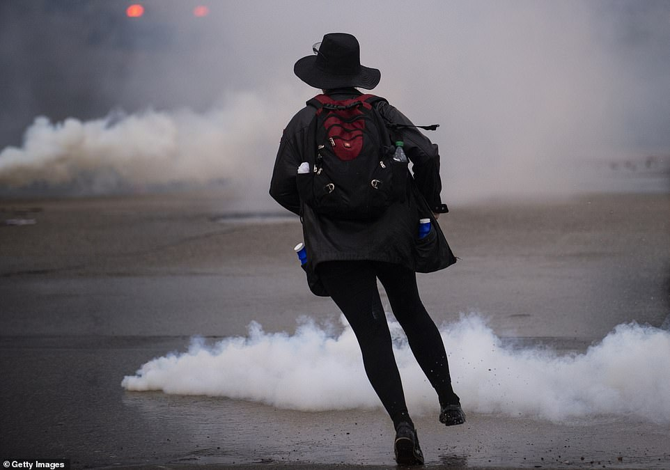 A protester runs through tear gas after police threw gas canisters to disperse the crowds