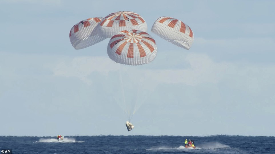 SpaceX's Crew Dragon descends to the Atlantic Ocean for a splashdown after a deorbit burn to reenter Earth's atmosphere during a test run in March 2019