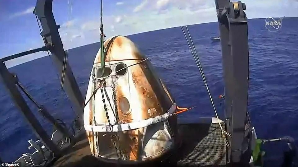 The blackened but otherwise perfectly intact capsule (pictured) was lowered into the water by four red and white parachutes that deployed from within the nose of the spacecraft during a test of the Crew Dragon capsule in March last year
