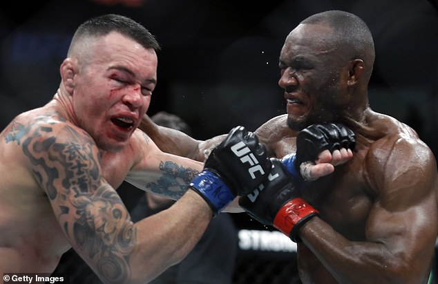Usman (right) broke Colby Covington's jaw (left) in his first title defence in December 2019