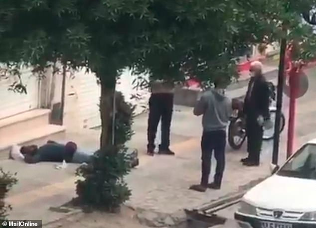 A man lies unconscious on the pavement while passers-by look on in Bushehr, Iran