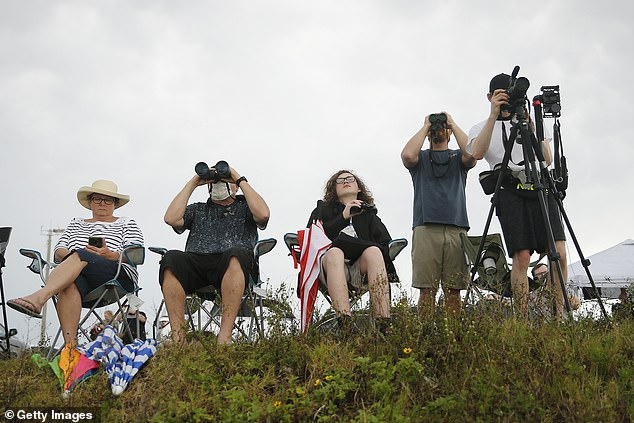 Spectators wait for a SpaceX launch which never took place last night after the mission was postponed because of bad weather