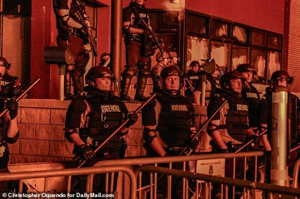 State cops wielded batons and wore body armour and helmets as they lined up against the rioters