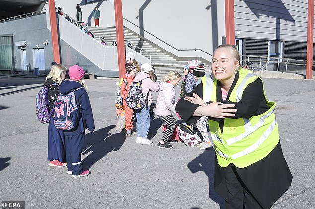FINLAND: A teacher signals a warm welcome as children arrive to start the primary school in Helsinki, Finland, after schools were reopened on Thursday, May 14