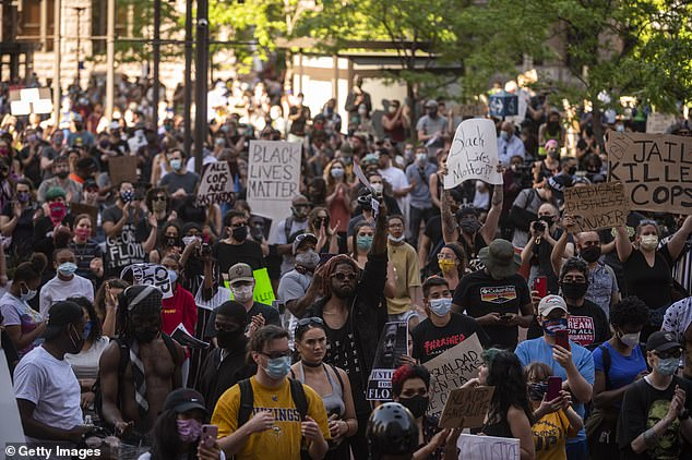 White police officer Derek Chauvin knelt on Floyd's neck for eight minutes until he passed out and later died earlier this week. Pictured: Protests in Minneapolis yesterday