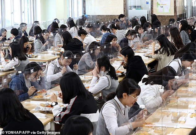 Students sit behind protective screens as they eat their lunch as a preventative measure against COVID-19 at a high school in Daejeon on May 20, 2020