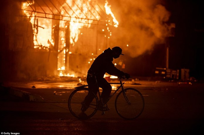 A fire burns at a gas station in Minneapolis, Minnesota, yesterday with protests ongoing in the state and around the country