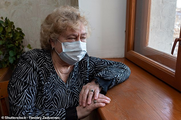 Parents caring for children or other vulnerable family members who need to shield will have to stick to stringent social distancing. Pictured: An elderly woman in a protective mask