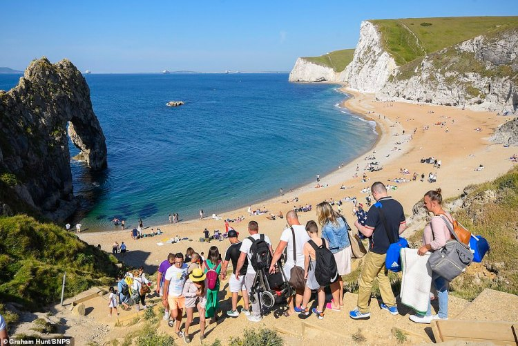 People are pictured descending on the beach at Durdle Door, Dorset, despite the council warning that it is closed today