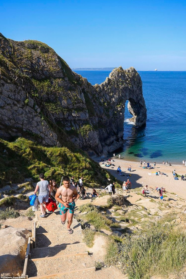 Visitors begin to arrive at Durdle Door at Lulworth in Dorset at the start of another day of scorching hot sunshine with sunbathers heading to the beauty spot despite warnings not to do so