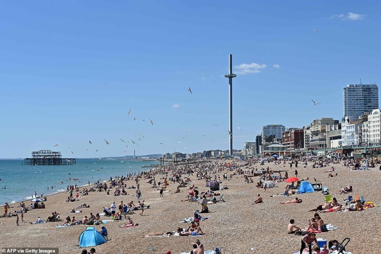 Sunseekers are pictured on Brighton beach today as the UK prepares to further ease lockdown rules tomorrow and temperatures soar
