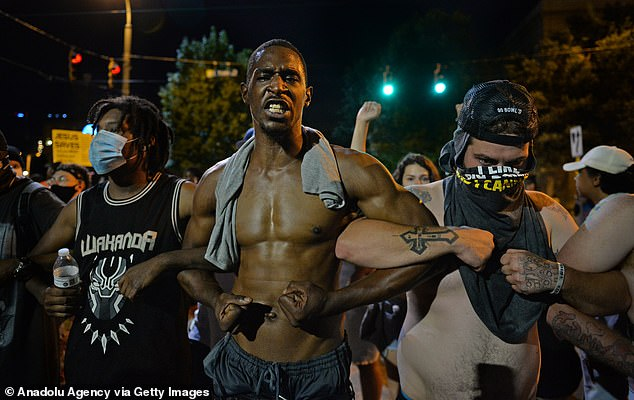 Charlotte, North Carolina: Demonstrators are seen locking arms during a protest on Saturday night in downtown Charlotte